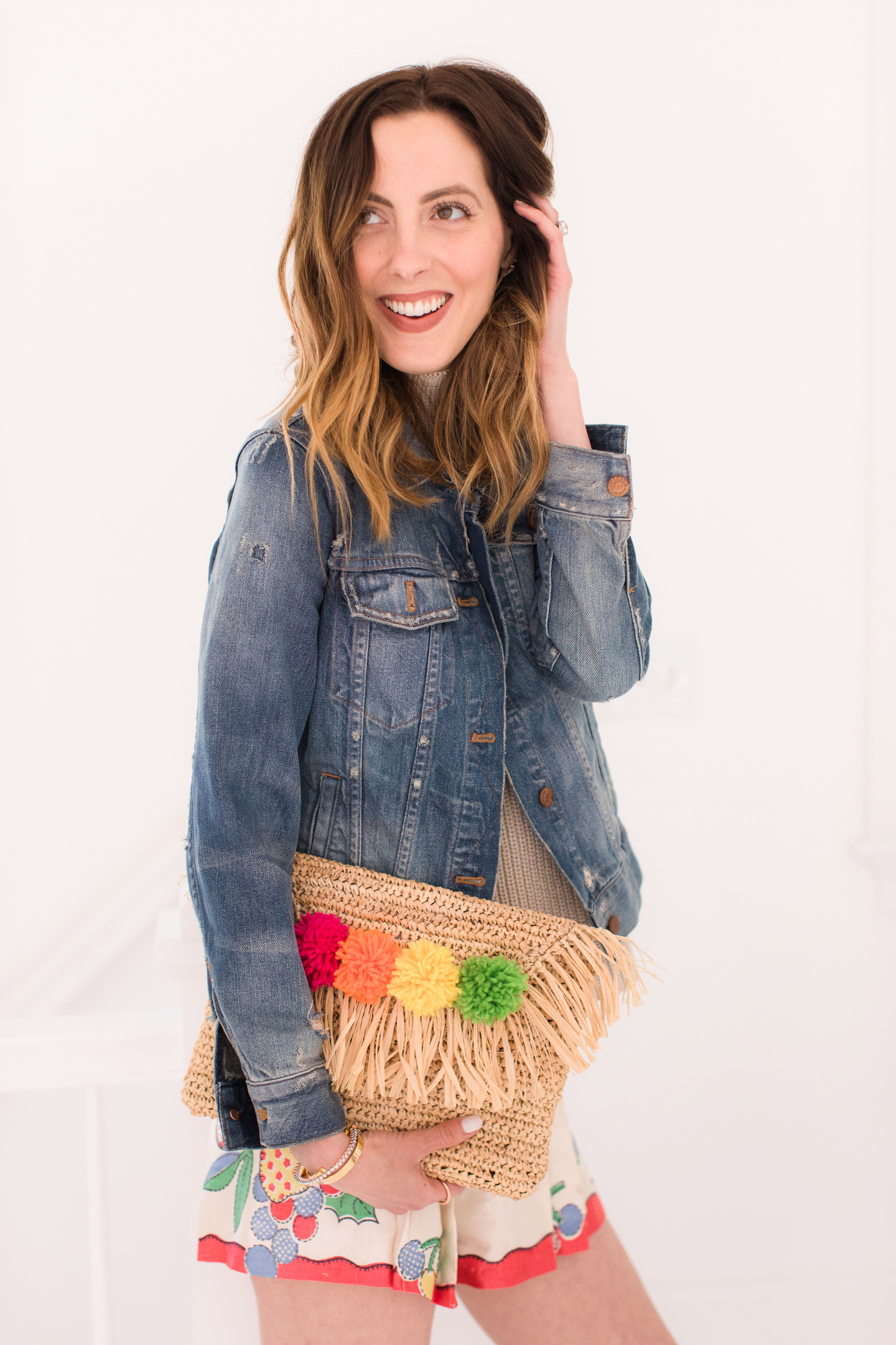 Eva Amurri Martino carries her multicolored DIY pom pom clutch with her colorful summer outfit
