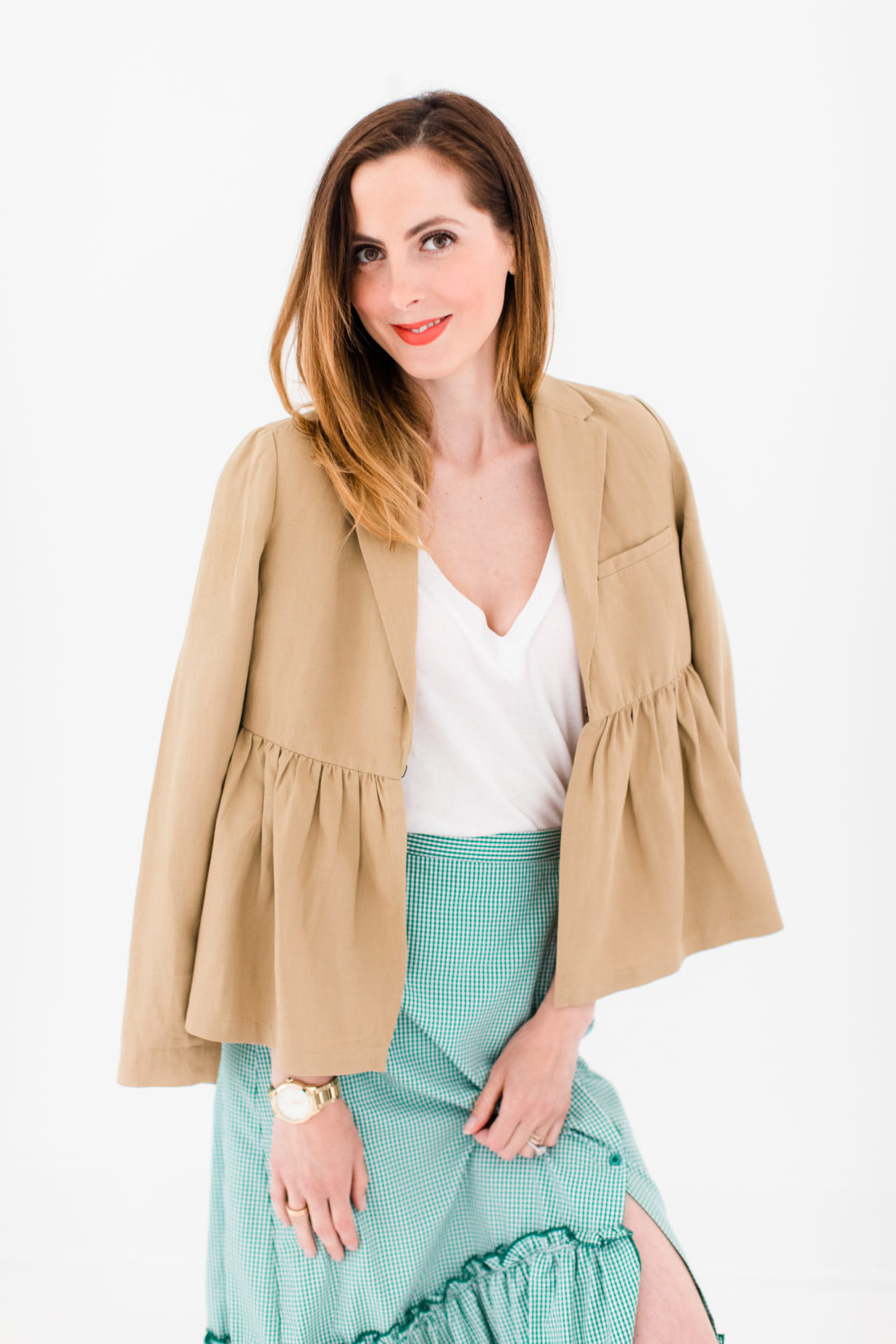 Eva Amurri Martino wears a green gingham ruffled skirt, white Tee, and tan ruffled jacket by BURU as part of a post about how to pack a suitcase