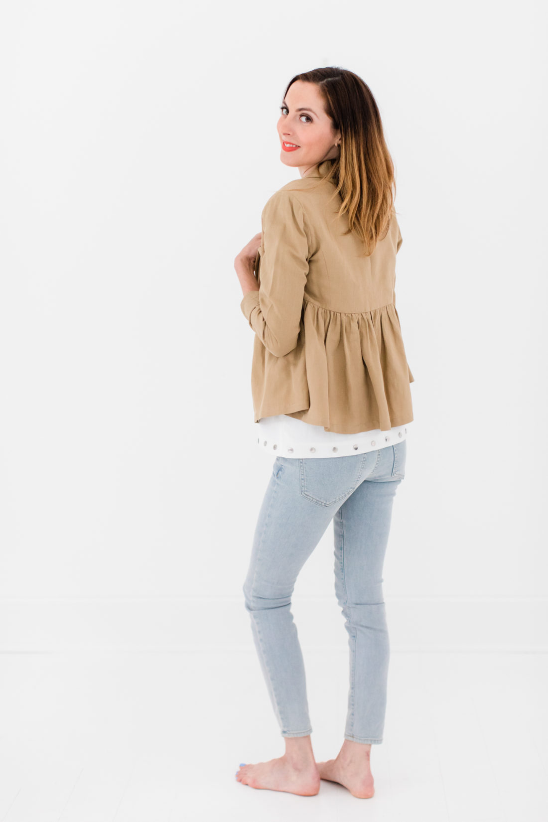 Eva Amurri Martino wears a white bow top, camel ruffle jacket, and jeans as part of a post about packing simply