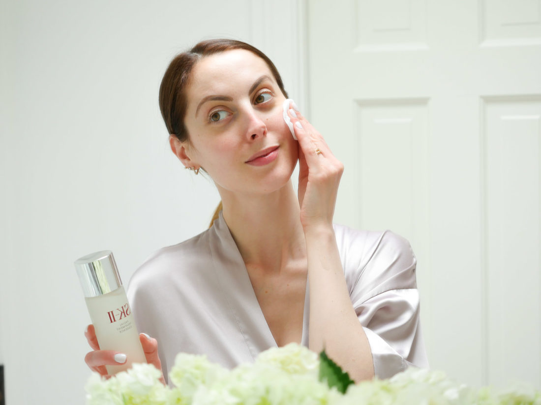 Eva Amurri Martino wears a lilac silk robe and applies SKII facial treatment essence with a cotton pad