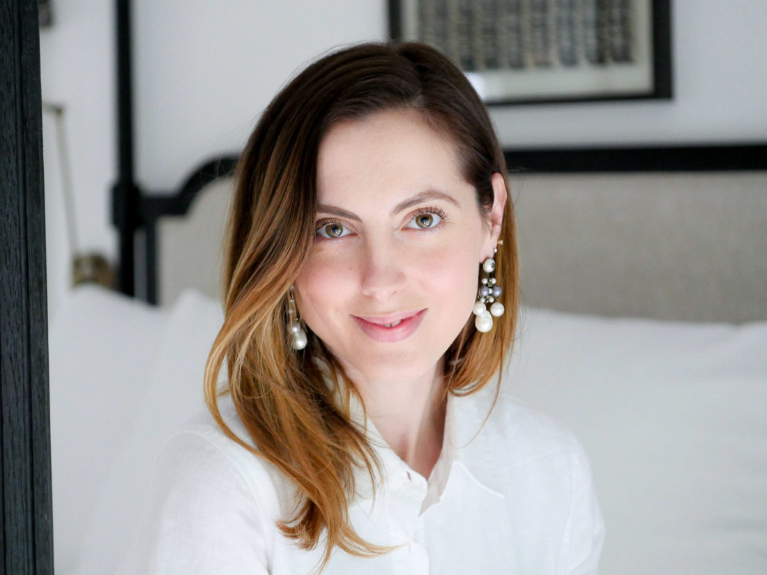 "Eva Amurri Martino sits on her bed wearing a white shirt dress, in an ""after"" pic from using SKII Facial Treatment Essence"