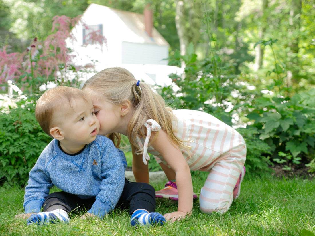 Marlowe Martino leans in to kiss her baby brother Major on the grass in Bar Harbor Maine