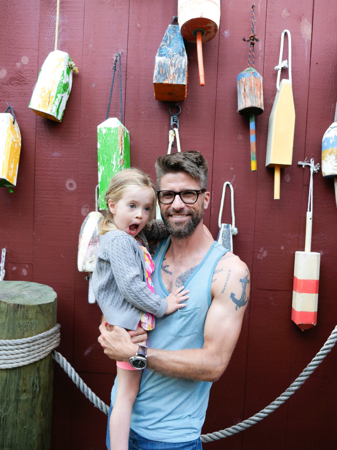 Kyle Martino and daughter Marlowe stand in front of a wall of multicolored buoys in downtown Bar Harbor, ME