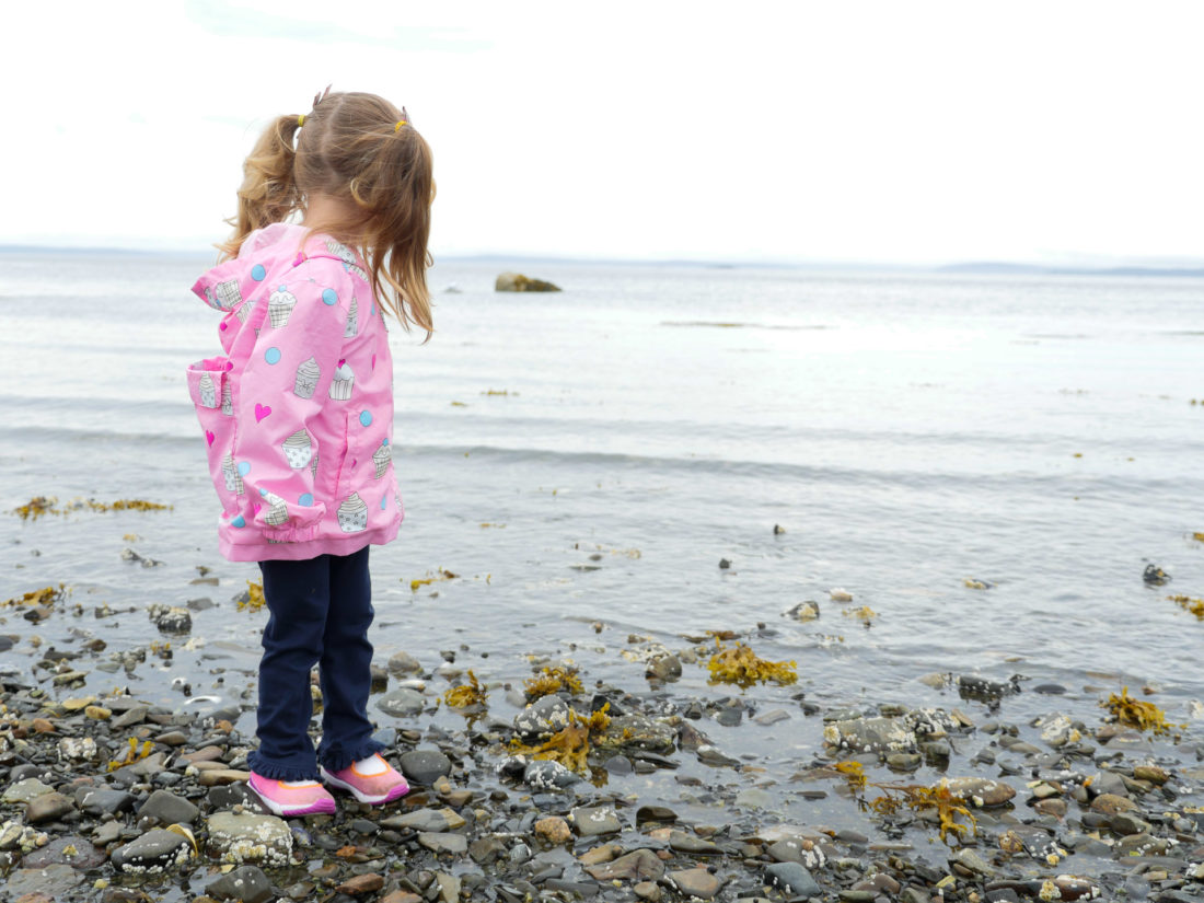Marlowe Martino wears a pink raincoat and walk on the beach in the Bar Harbor Area of Maine