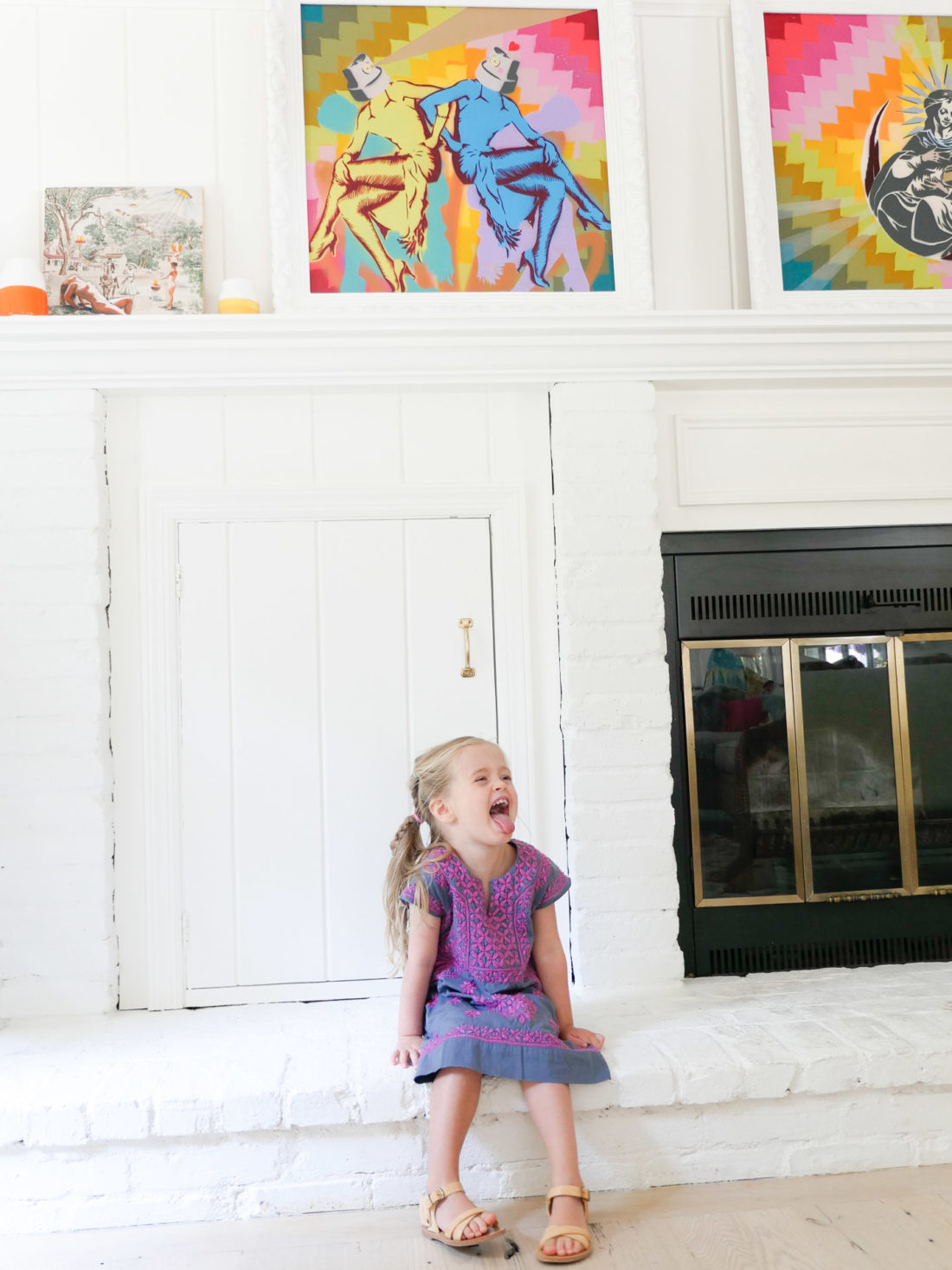 Marlowe Martino sticks her tongue out on the hearth of the fireplace in the family room of her Connecticut home