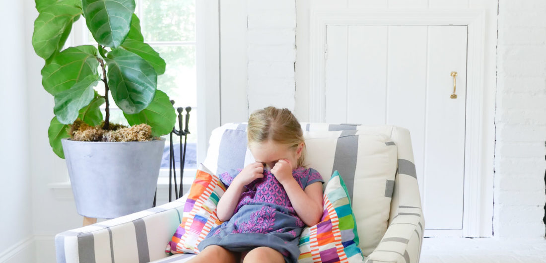 Marlowe Martino wears an embroidered dress and sits in a striped armchair in the family room of her Connecticut home
