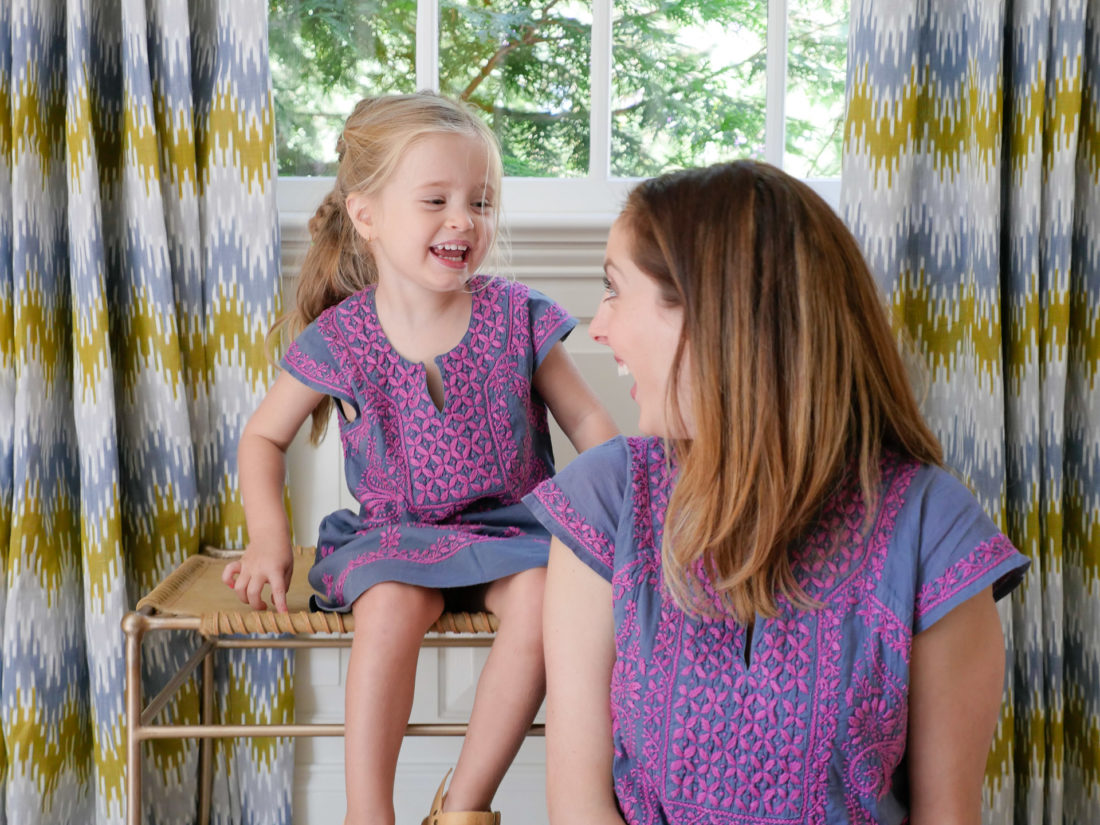Eva Amurri Martino and Marlowe Martino wear matching embroidered dresses and sit together in the living room of their Connecticut home