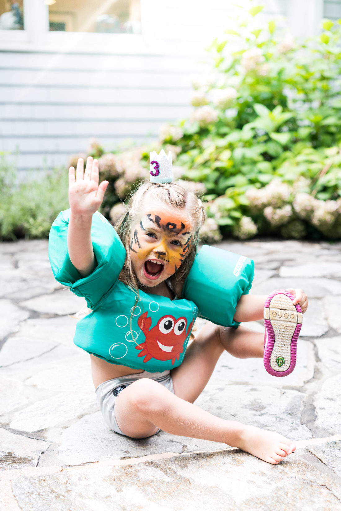 Marlowe Martino wears a birthday crown and tiger face paint at her third birthday party