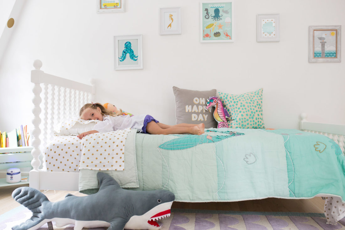 Marlowe lays on her Big Girl Bed in her mermaid themed bedroom in Connecticut