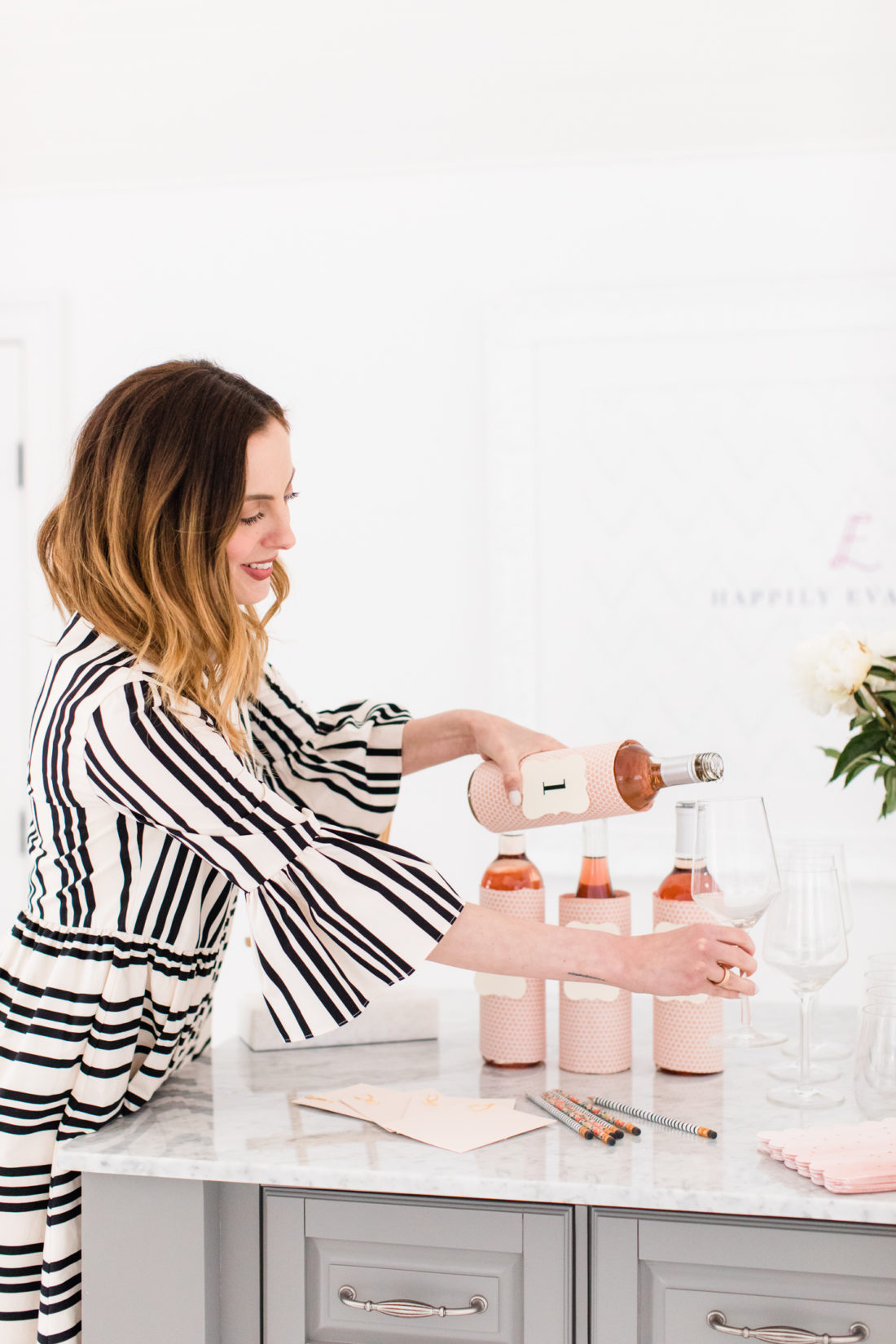 Eva Amurri Martino wears a black and white striped dress and pours a glass of Rosé wine