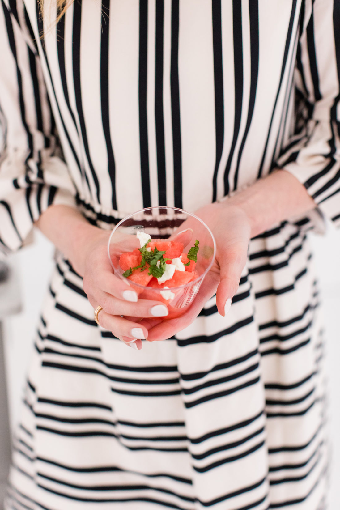 Eva Amurri Martino wears a black and white striped dress and holds an individually-portioned watermelon and mint salad at the Rosé Tasting party at her Connecticut home