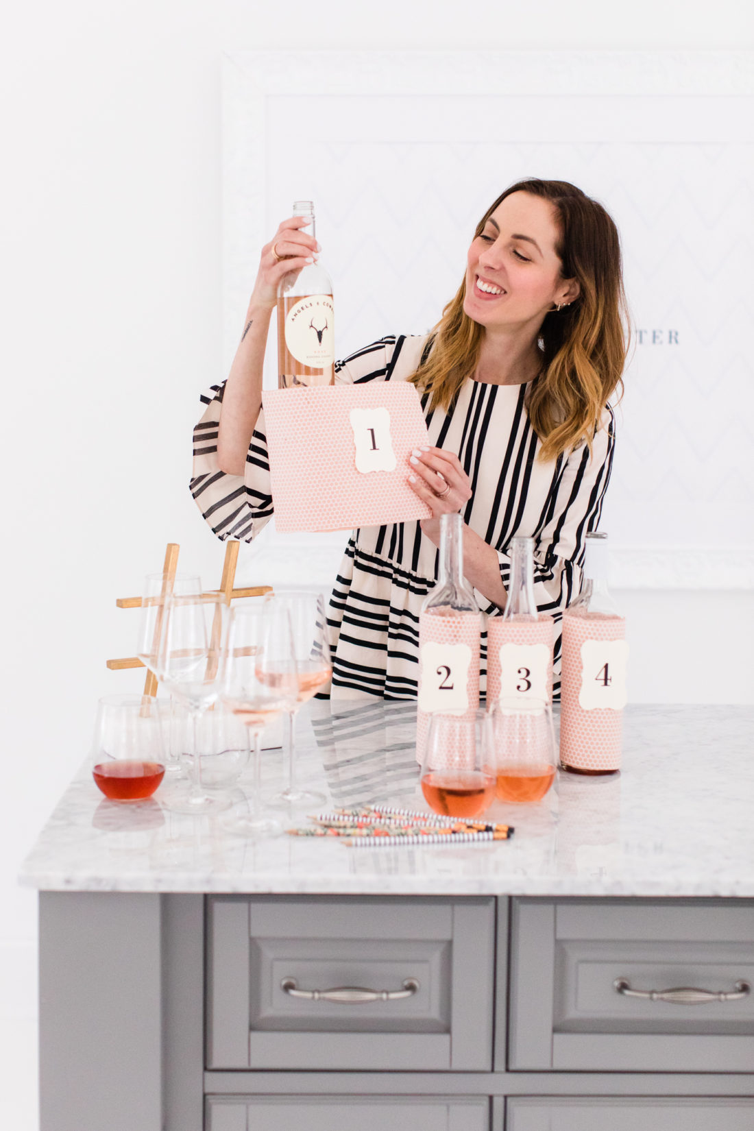 Eva Amurri Martino removes the wine bottle coverings to reveal the true wines behind the taste tests at her Rosé Tasting Party