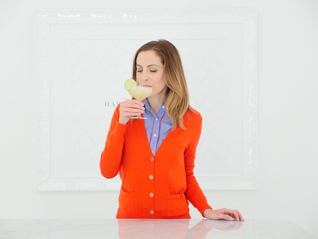 Eva Amurri Martino wears a red sweater and takes a sip of a frosty margarita