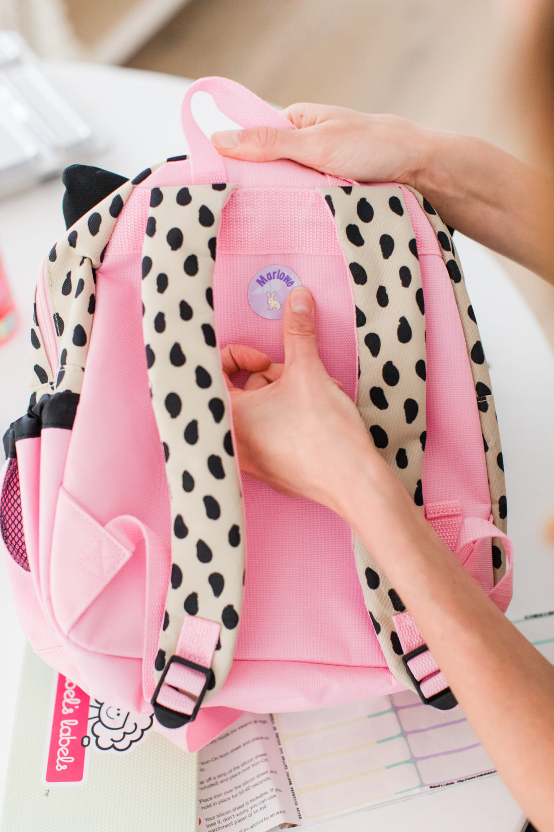 Eva Amurri Martino labels a kitty cat backpack as she prepares to send three year old daughter Marlowe off to preschool
