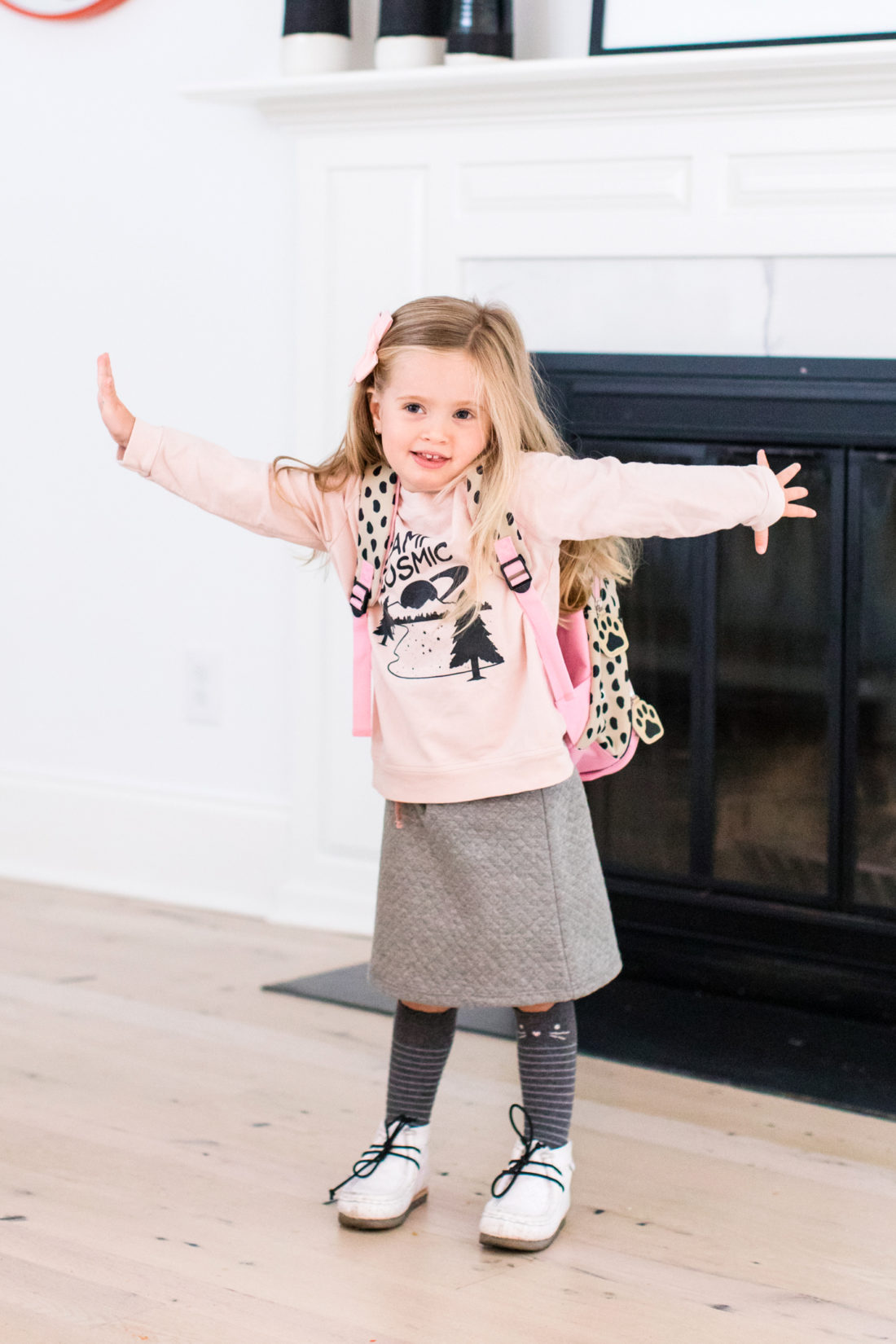 Marlowe Martino wears a pink sweatshirt and grey skirt with a pink bow in her hair, as she prepares to head off to the first day of Preschool