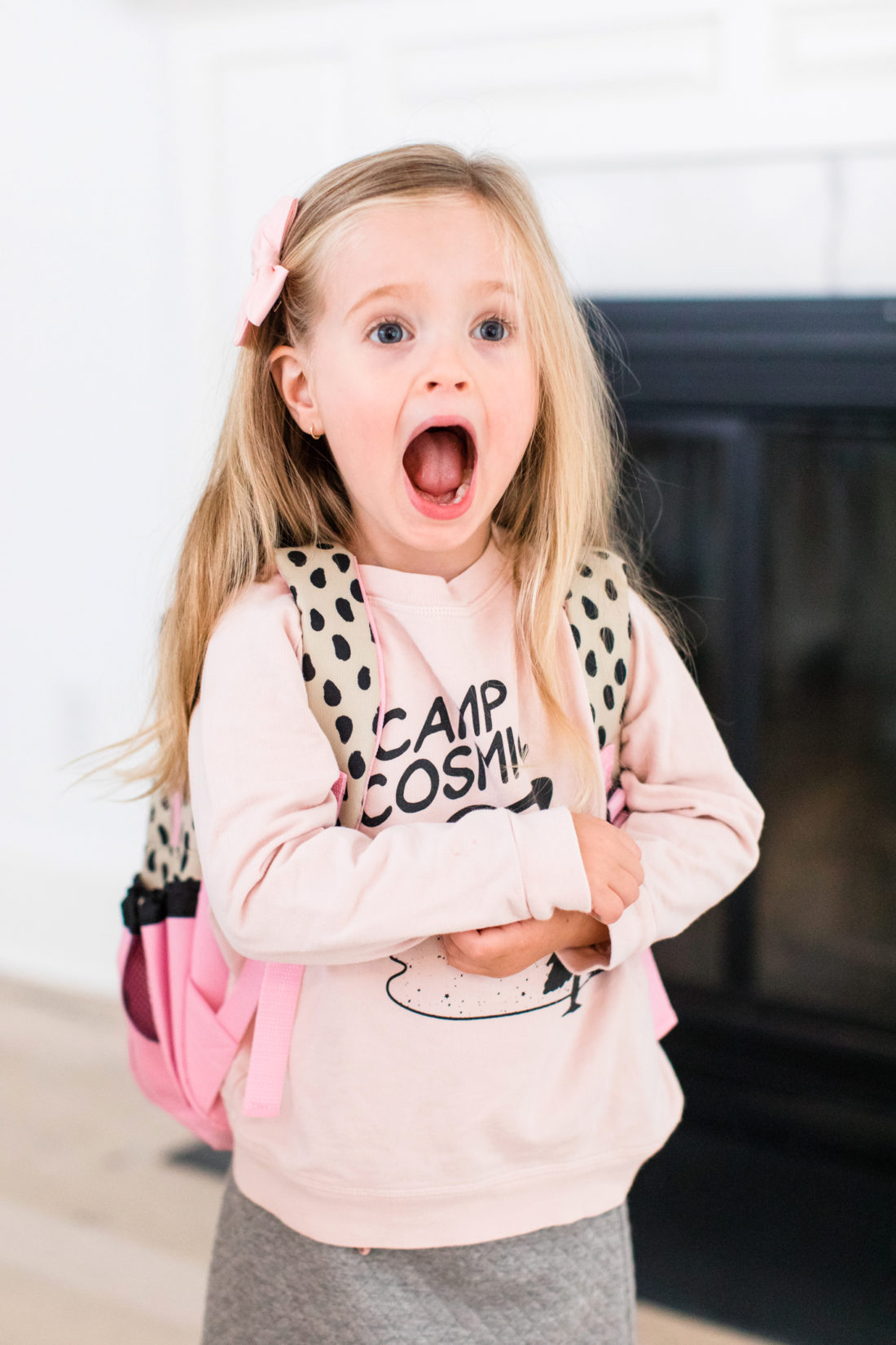 Marlowe Martino wears a pink sweatshirt and looks surprised as she gets ready to head off to her first day of preschool
