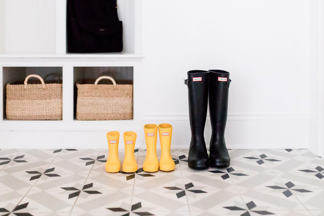 "A lineup of black and yellow ""Mommy and Me"" Hunter boots on the black and white tiled floor of Eva Amurri Martino's Connecticut mudroom"