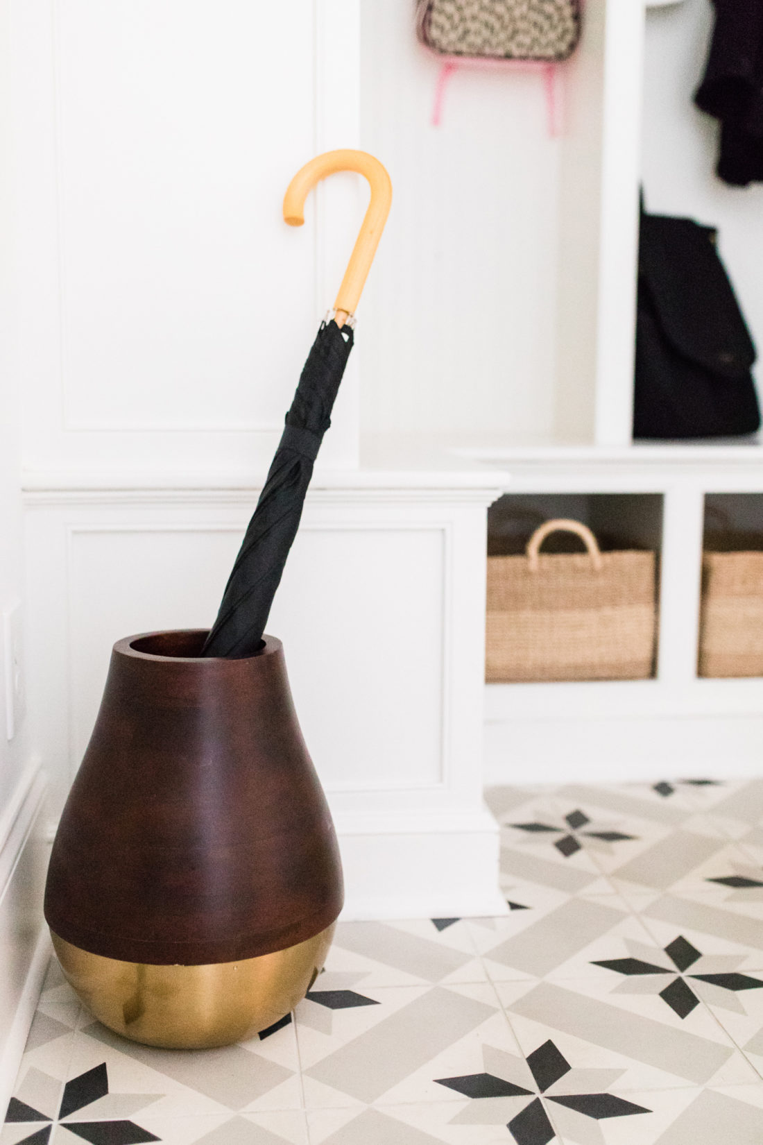 A wood and brass umbrella stand in the black and white tiled mudroom in Eva Amurri Martino's Connecticut home