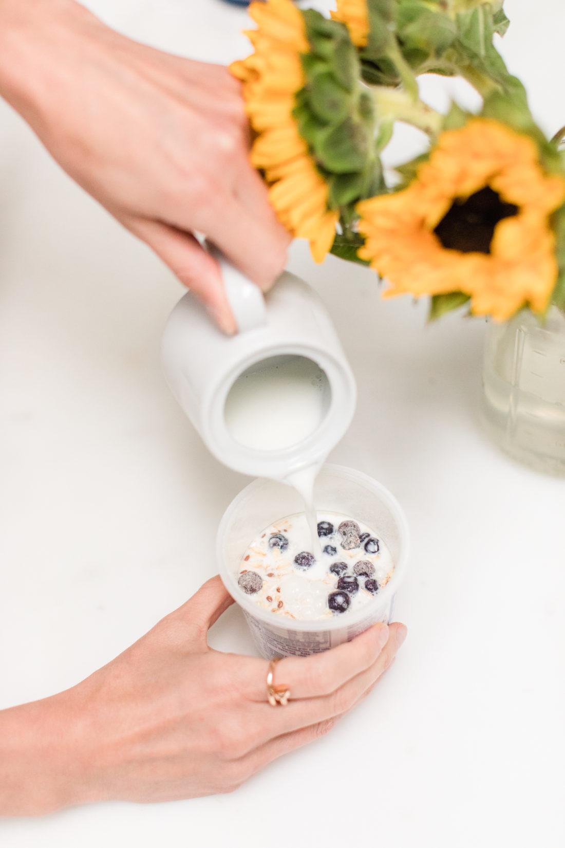 Eva Amurri Martino adds milk to a container of Quaker Overnight Oats