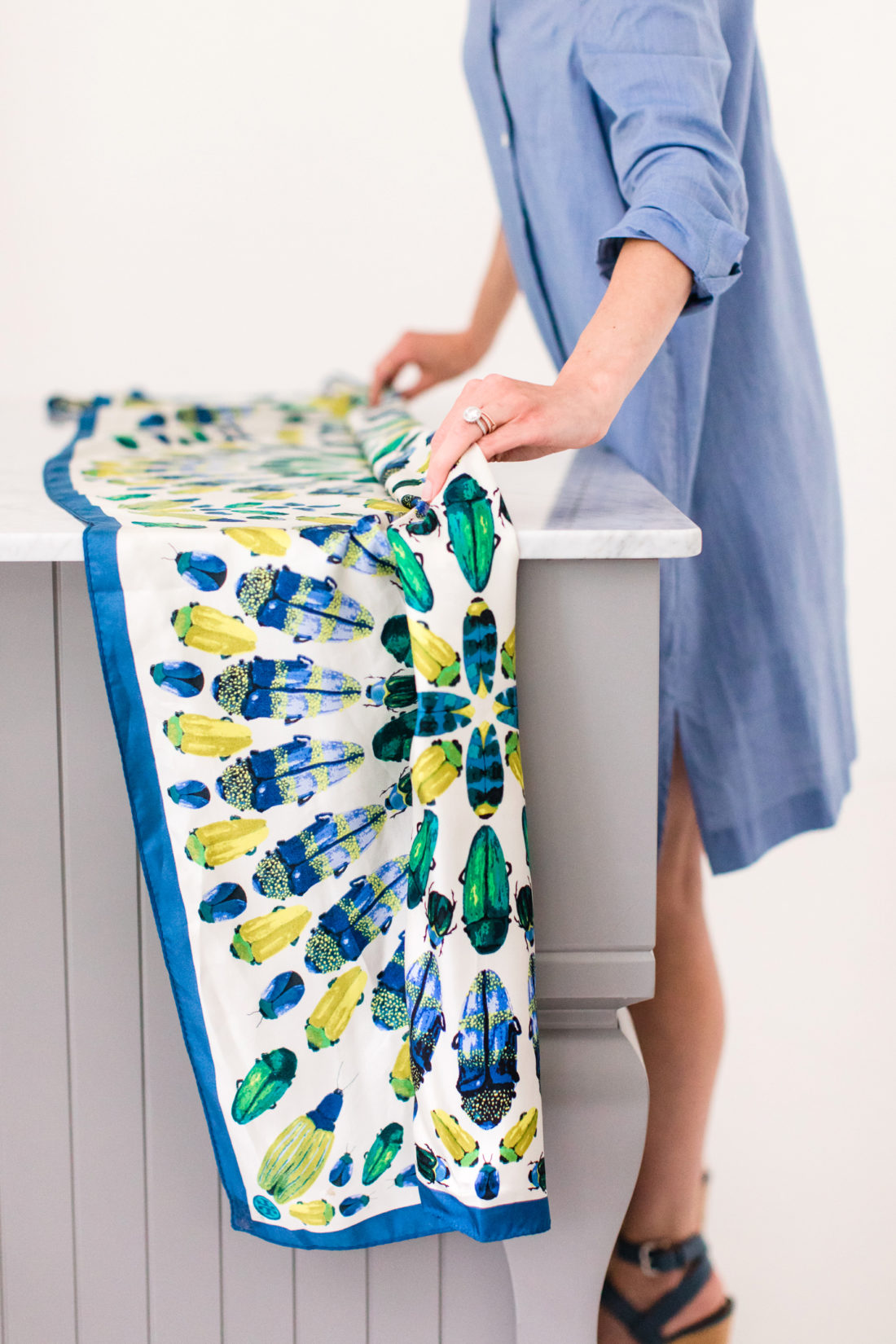 Eva Amurri Martino folds a long printed silk scarf in to a long strip as she prepares to tie it