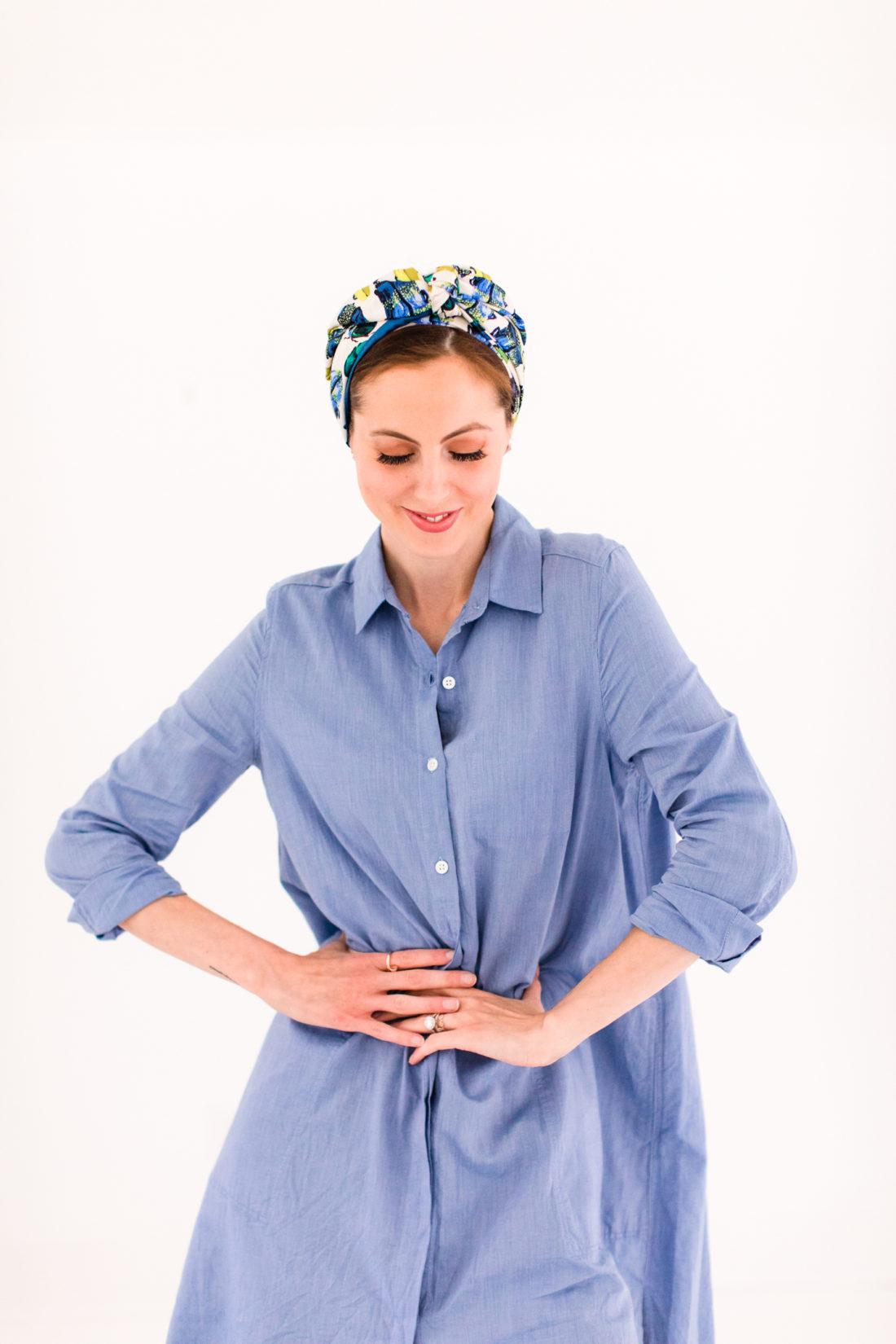 Eva Amurri Martino wears a light blue shirt dress and a turban head wrap made from a knotted silk scarf