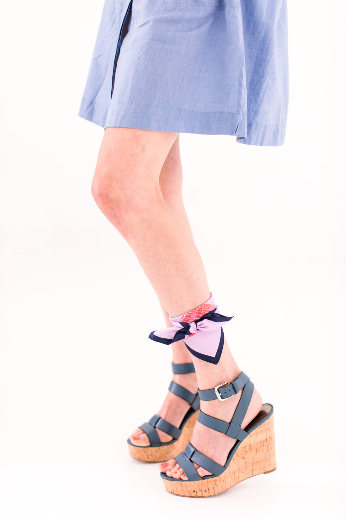 Eva Amurri Martino wears a light blue shirt dress and wraps a folded silk scarf around her ankle as an ankle accessory