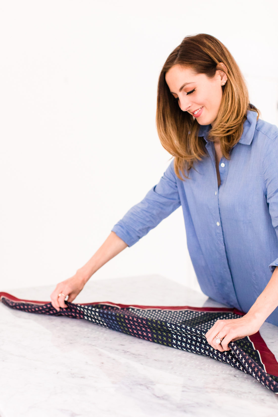 Eva Amurri Martino folds a patterned silk scarf to tie on her purse