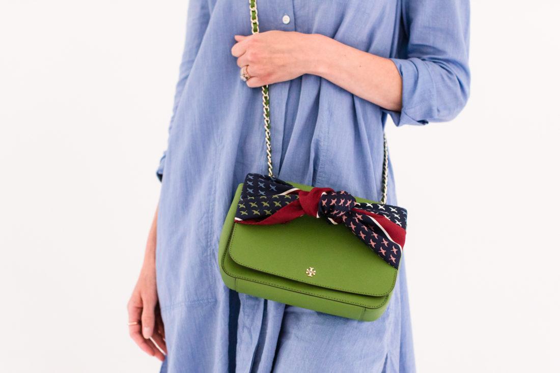 Eva Amurri Martino wears a blue shirt dress and styles a silk scarf to adorn her green tory burch bag