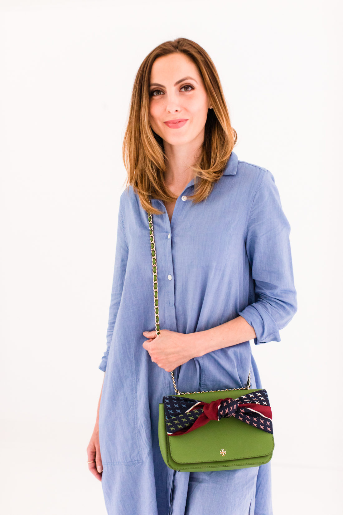 Eva Amurri Martino wears a blue shirt dress and styles a silk scarf to adorn her green tory burch bag