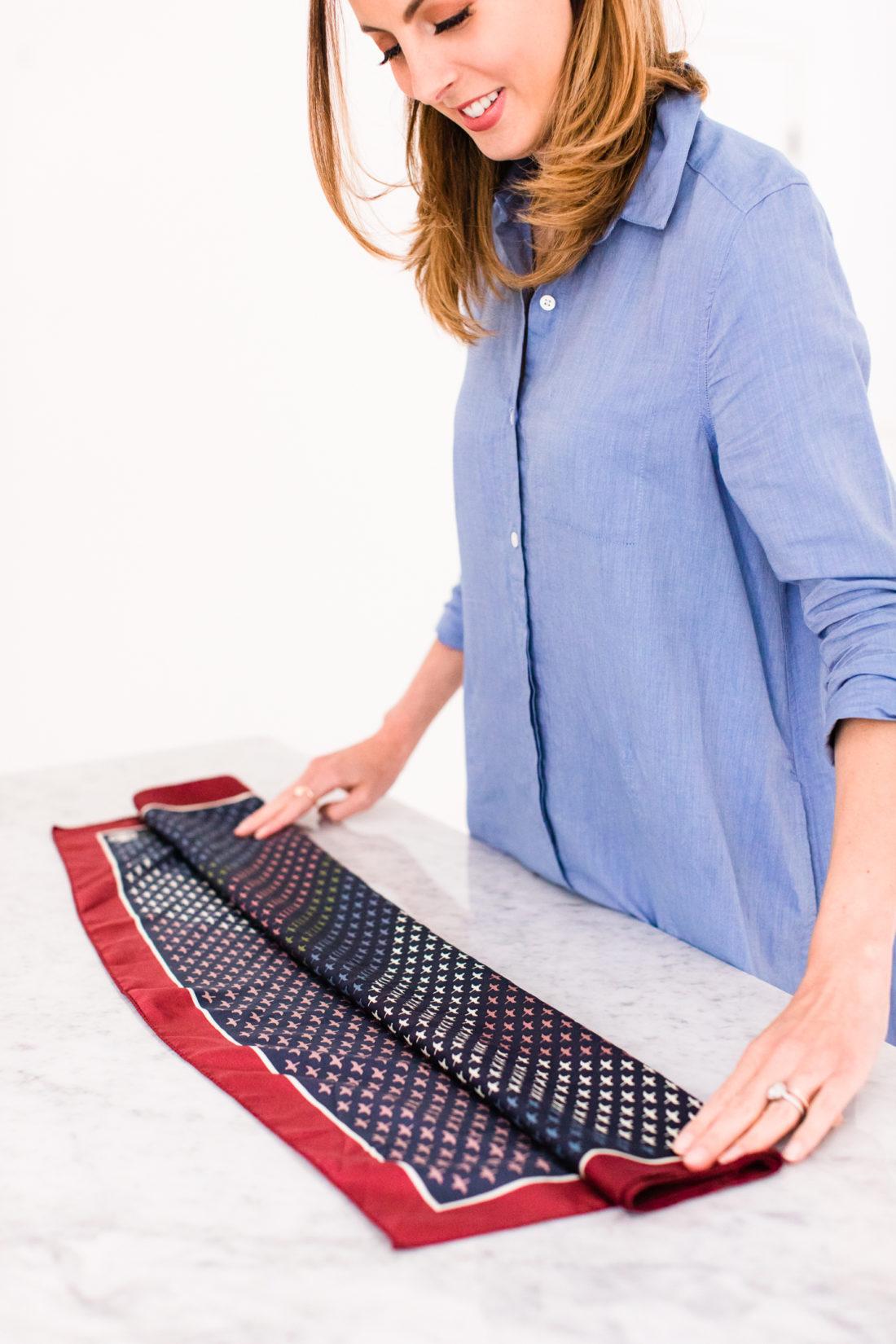 Eva Amurri Martino folds a printed silk scarf to tie around the strap of her purse