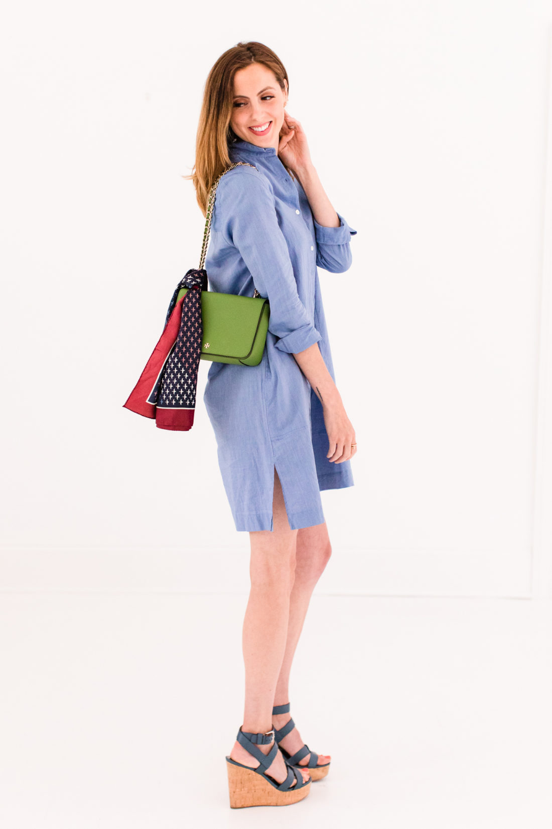 Eva Amurri Martino wears a light blue shirt dress and a green tory burch bag with a printed scarf tied around it