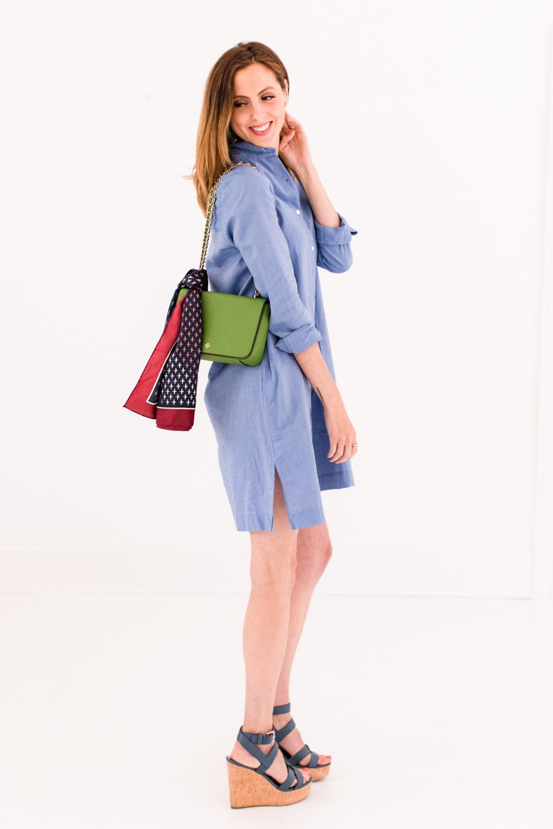 Eva Amurri Martino wears a light blue shirt dress and a green tory burch bag with a printed scarf tied around it