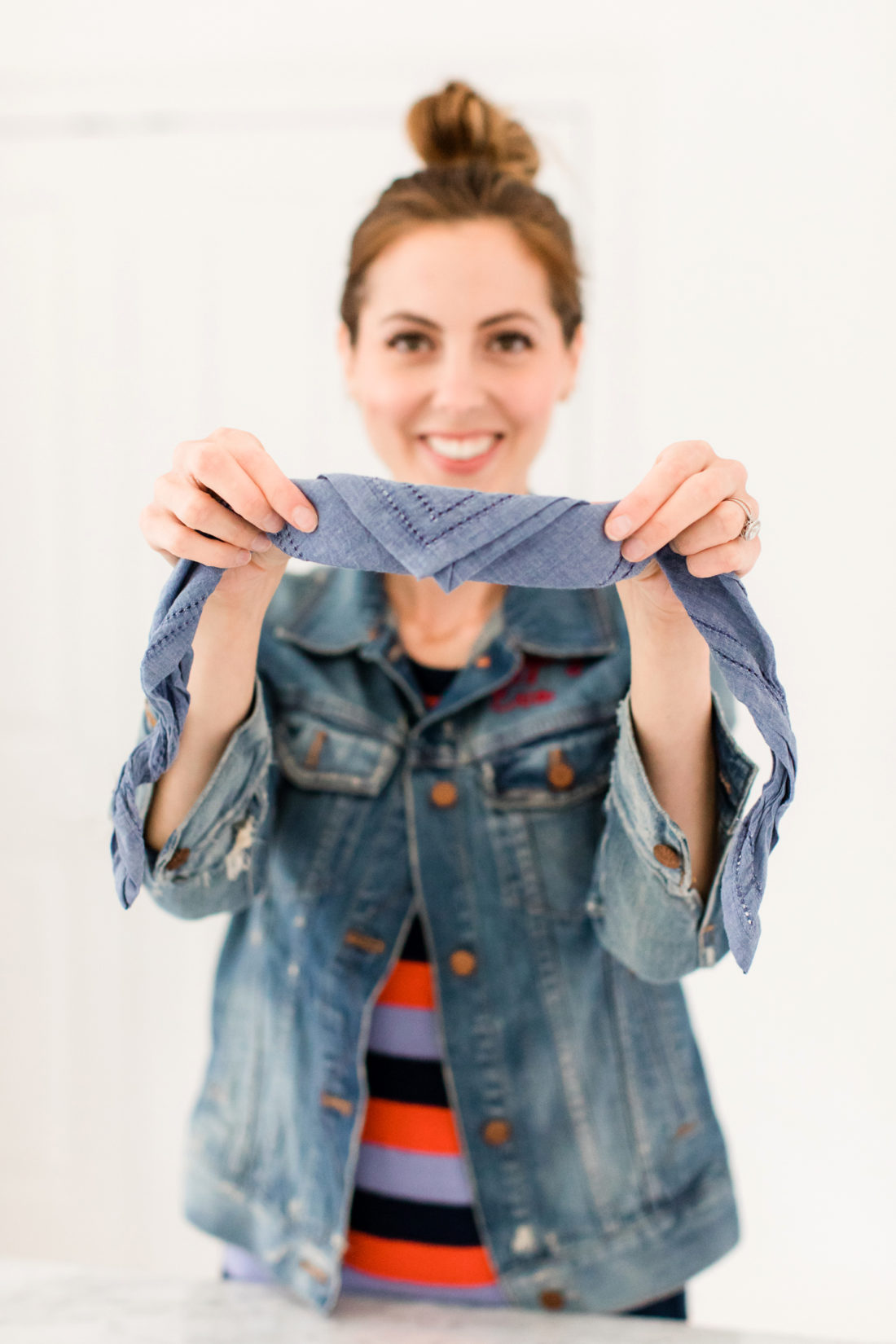 Eva Amurri Martino wears a striped dress and denim jacket, and prepares to tie a linen kerchief around her bun
