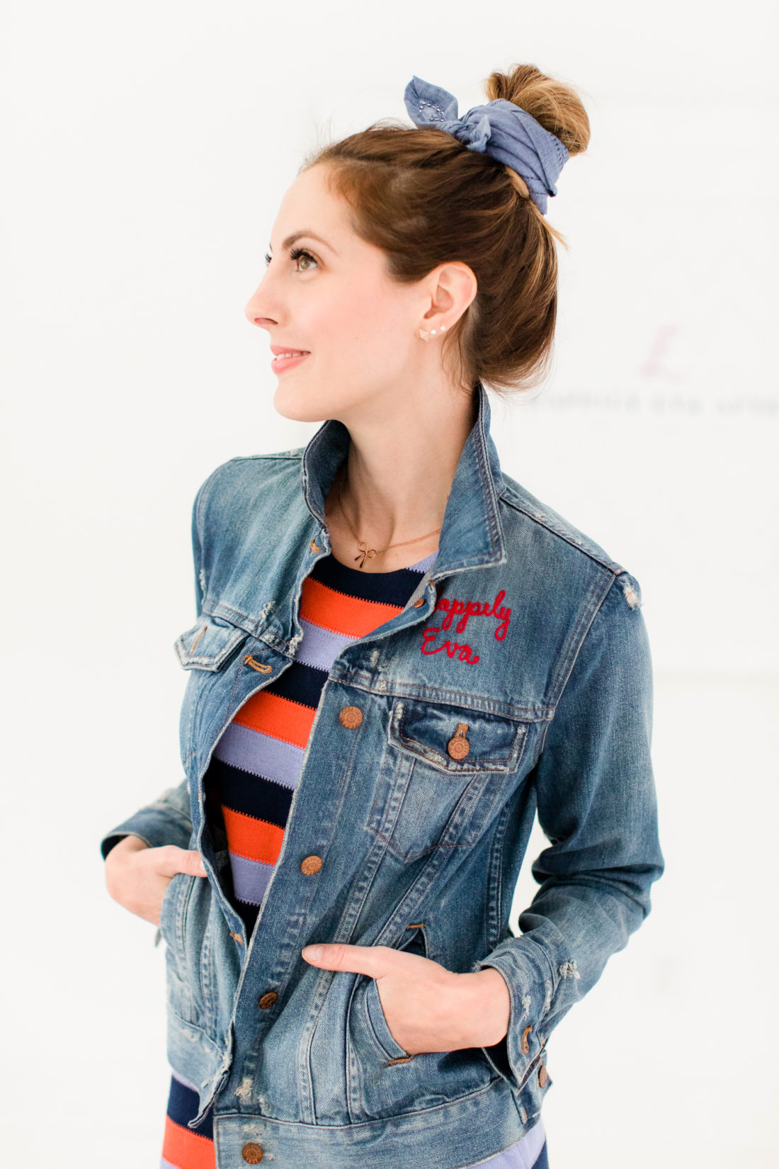 Eva Amurri Martino wears a striped dress and distressed denim jacket while rocking a kerchief bun hairstyle
