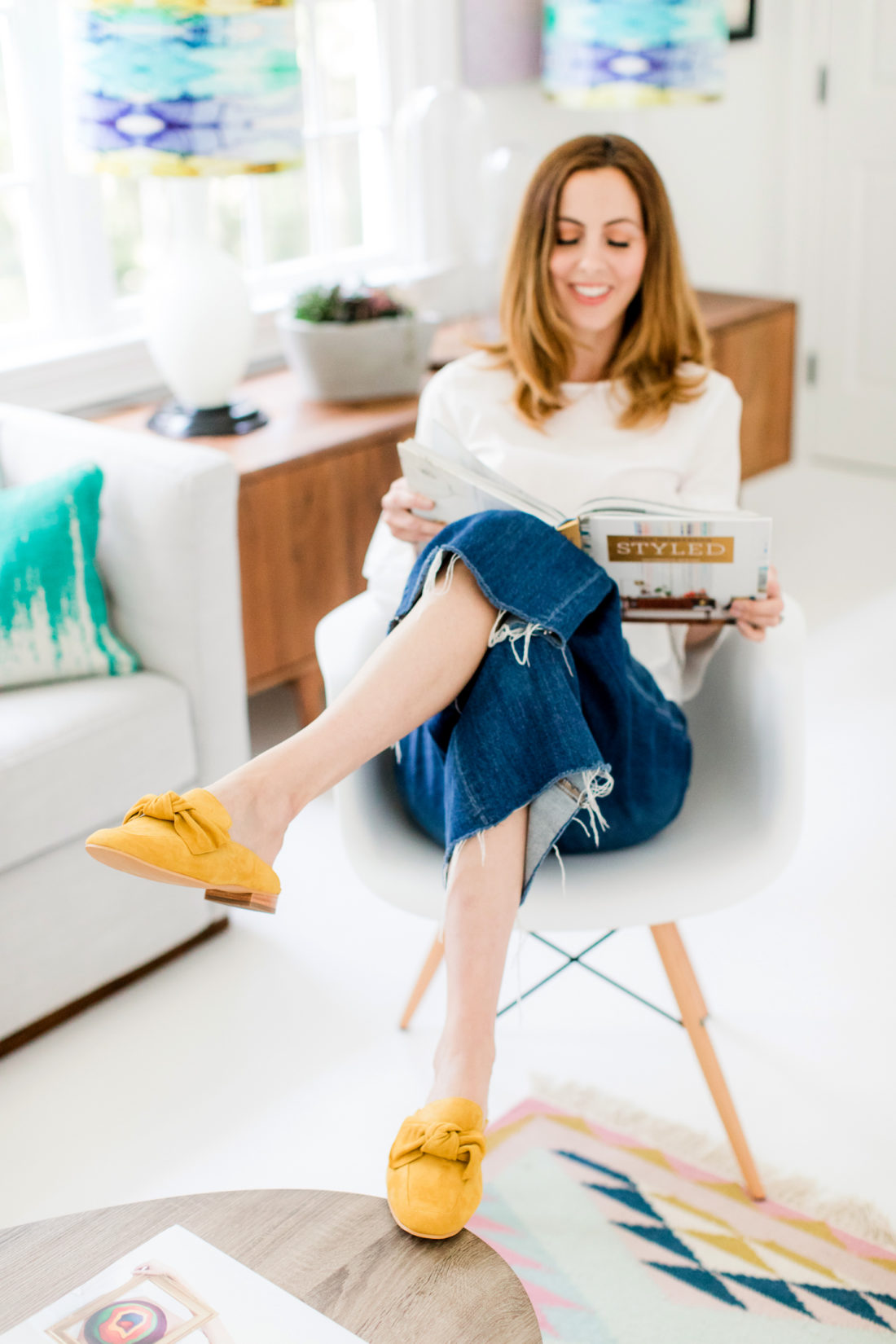 Eva Amurri Martino relaxes in her home office reading a book, wearing a white tiered top, frayed cropped denim, and mustard mules