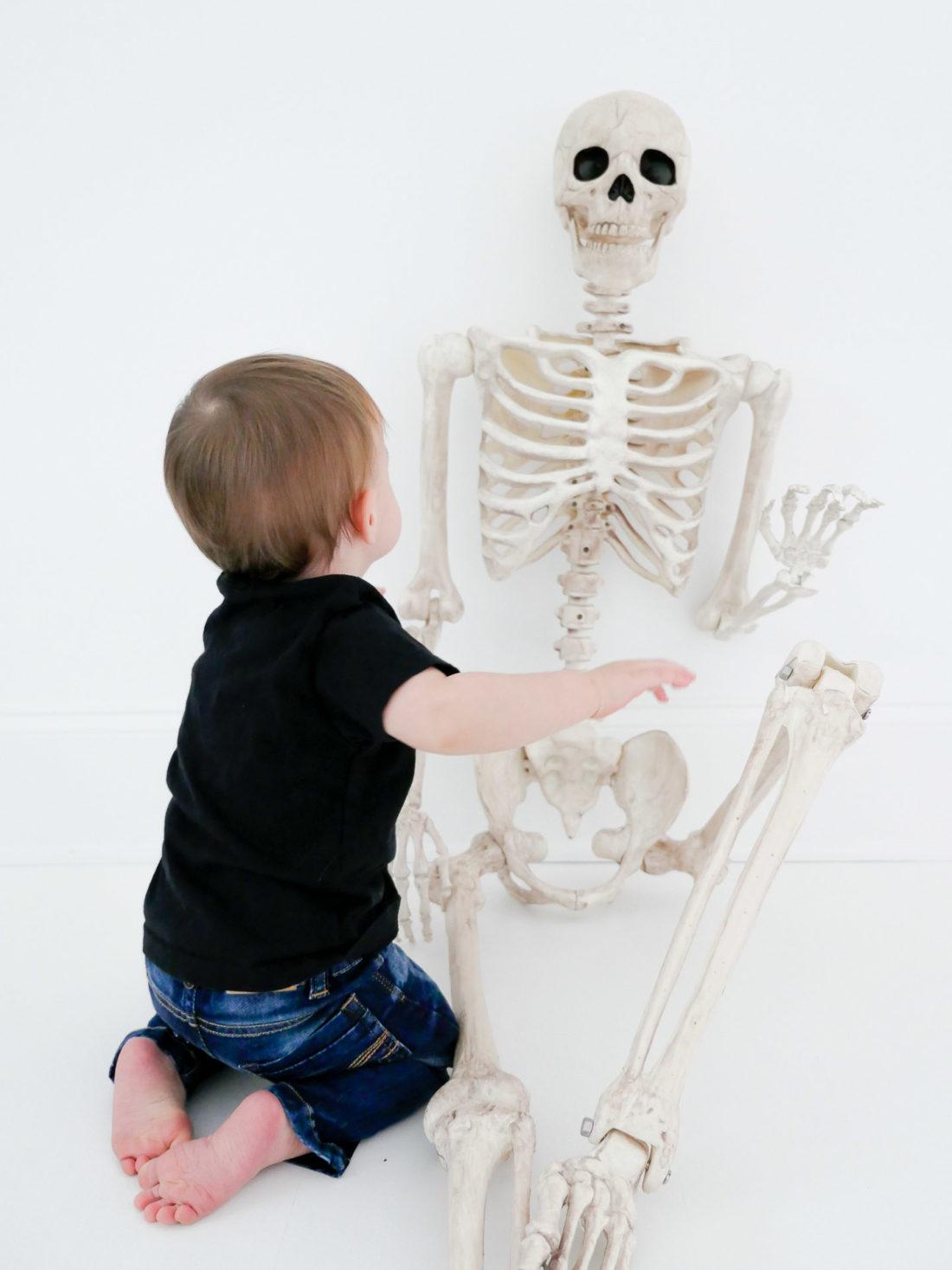 Major Martino wears a custom Halloween themed tee shirt and crawls towards a skeleton decoration