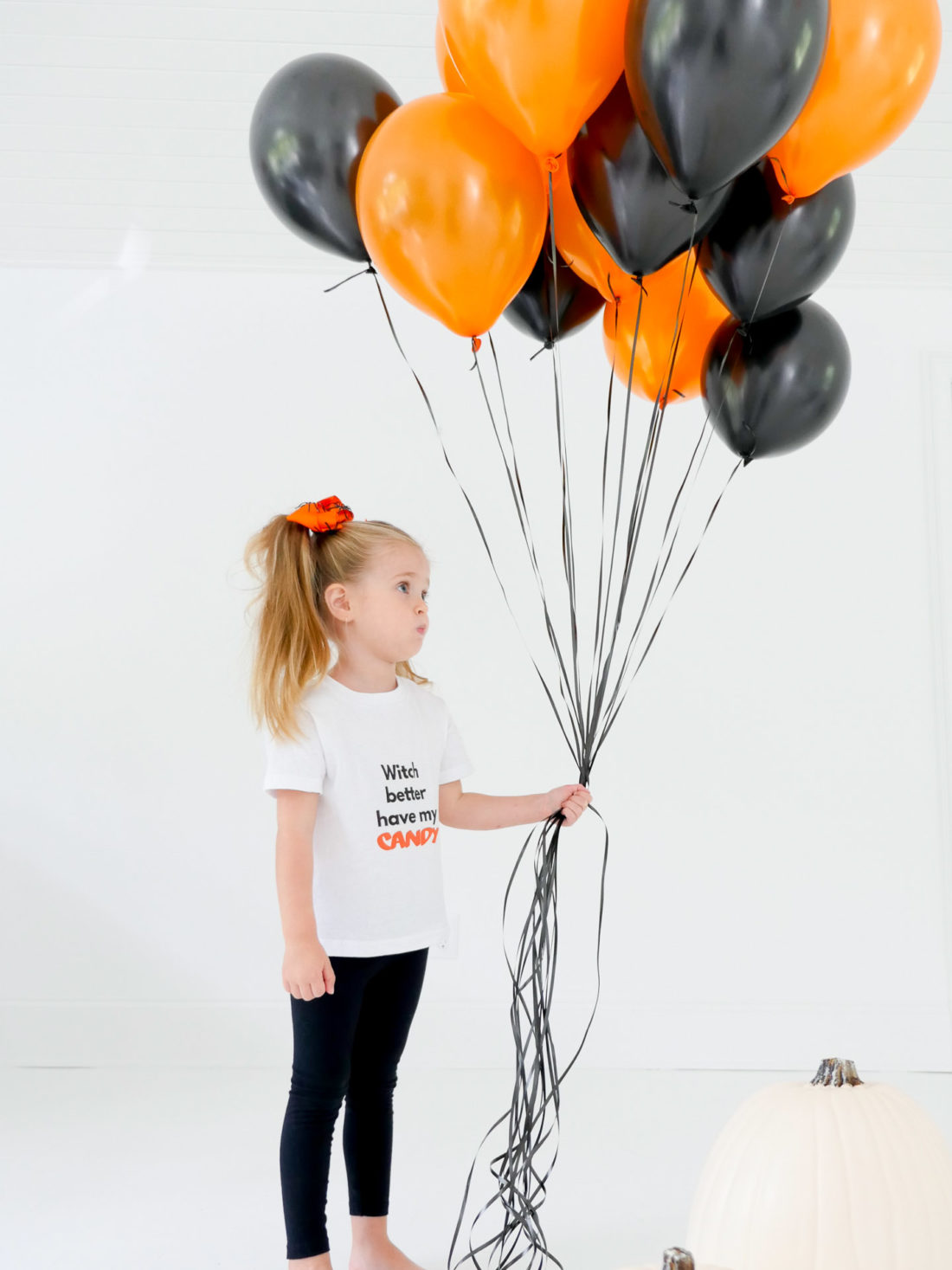 Marlowe Martino wears a festive Halloween tee shirt designed using The Happily App and holds a big bundle of orange and black balloons