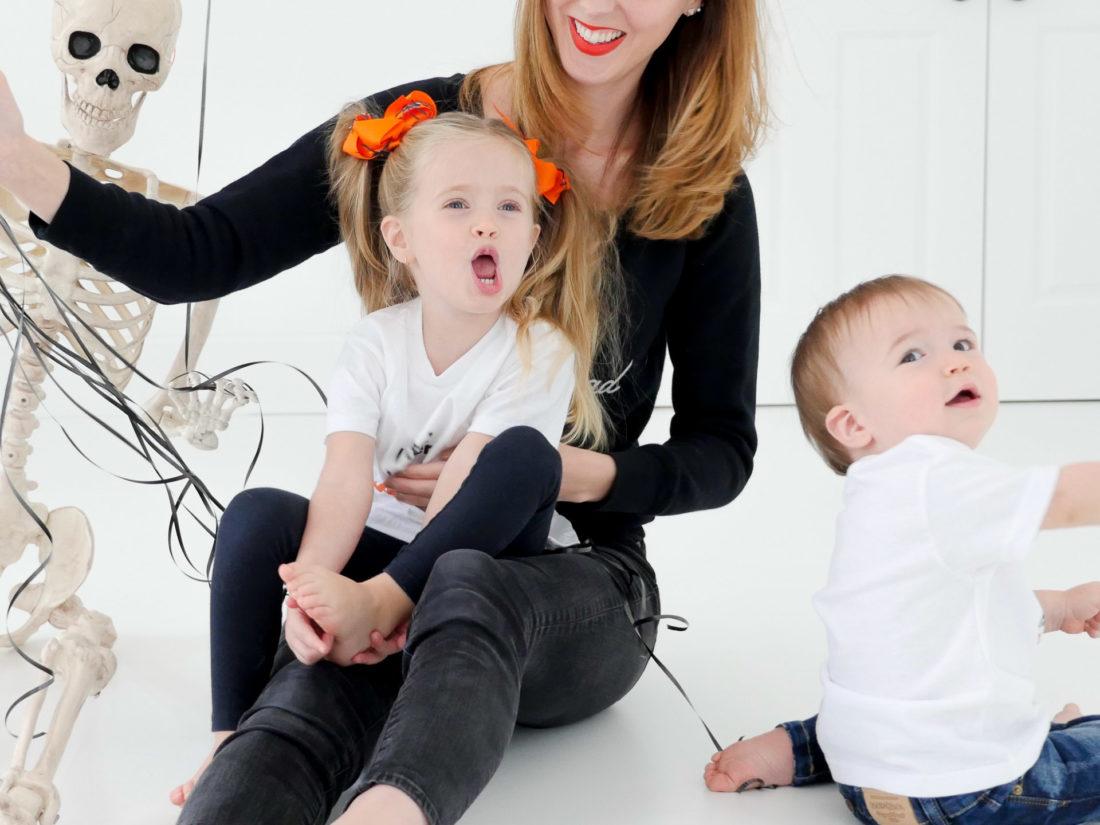 Eva Amurri Martino sits with children Marlowe and Major wearing custom Halloween themed tee shirts designed using The Happily App