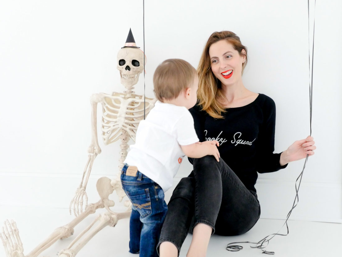 Eva Amurri Martino sits next to a festive skeleton, wearing a custom Halloween themed sweatshirt designed using The Happily App