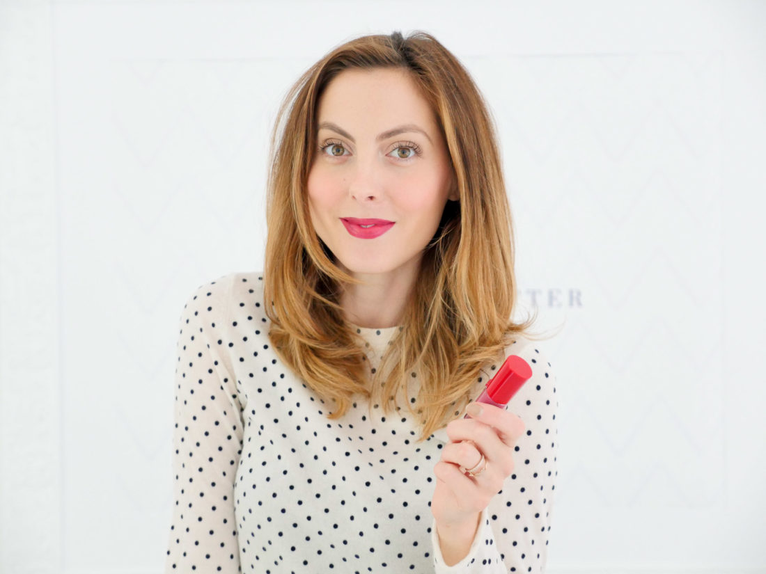 Eva Amurri Martino wears a white sweater with black polka dots, and a shiny berry lip