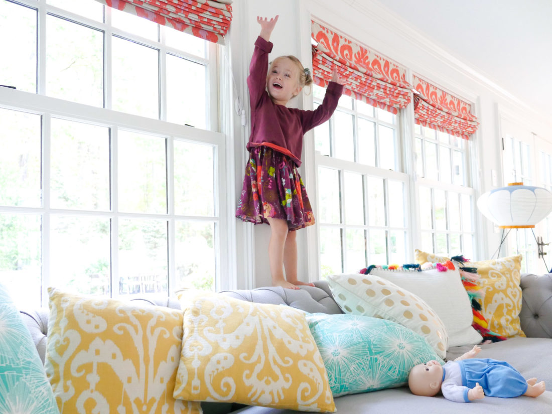 Marlowe Martino wears a multicolored dress and prepares to jump off the couch in her Connecticut home