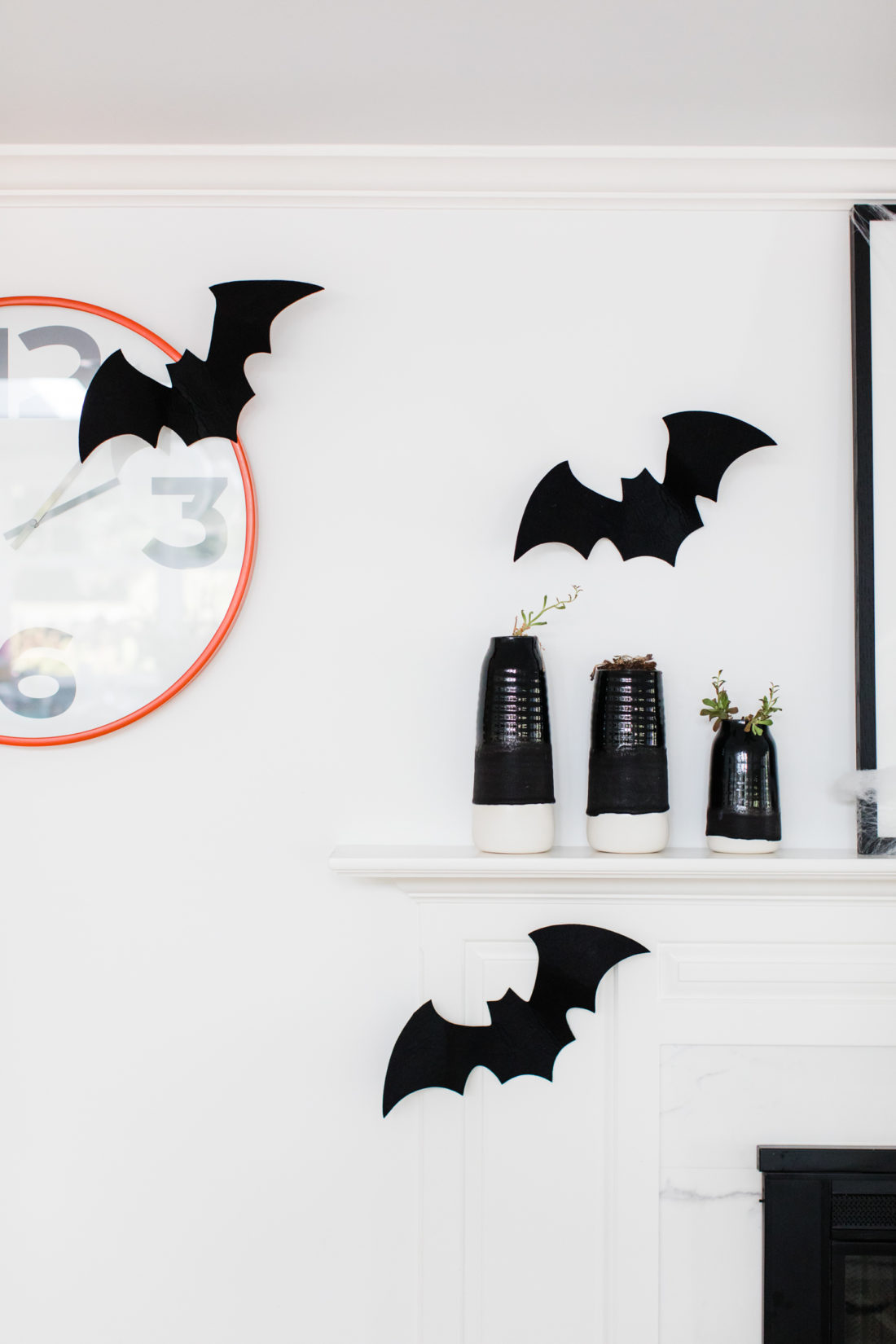 Felt bats fly around an orange clock in Eva Amurri Martino's Halloween decorated kitchen