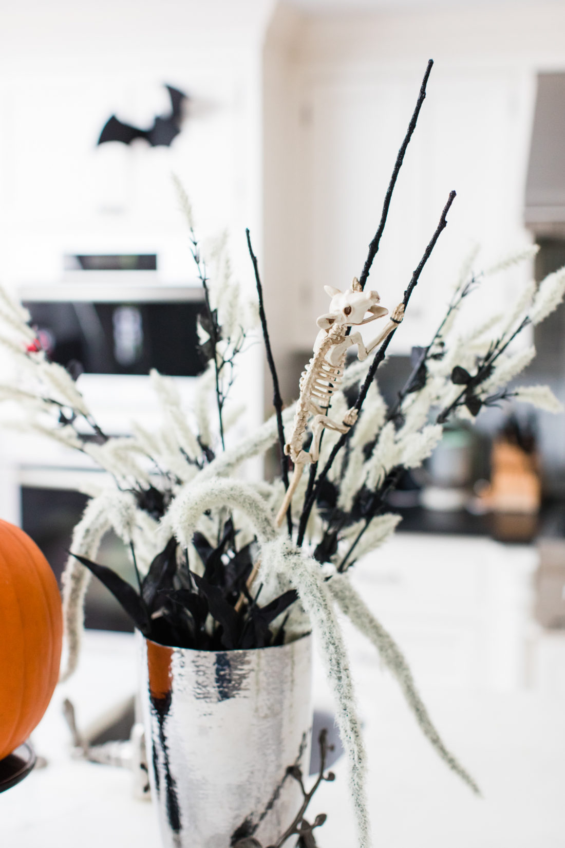 A mouse skeleton climbs up the reeds in a halloween themed flower display in Eva Amurri Martino's Connecticut kitchen