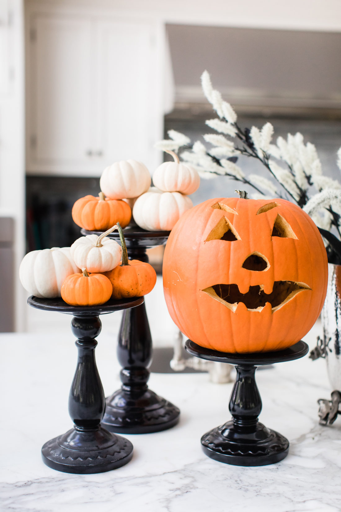 An assortment of Pumpkins on black lacquere stands decorate the marble island in Eva Amurri Martino's Connecticut kitchen