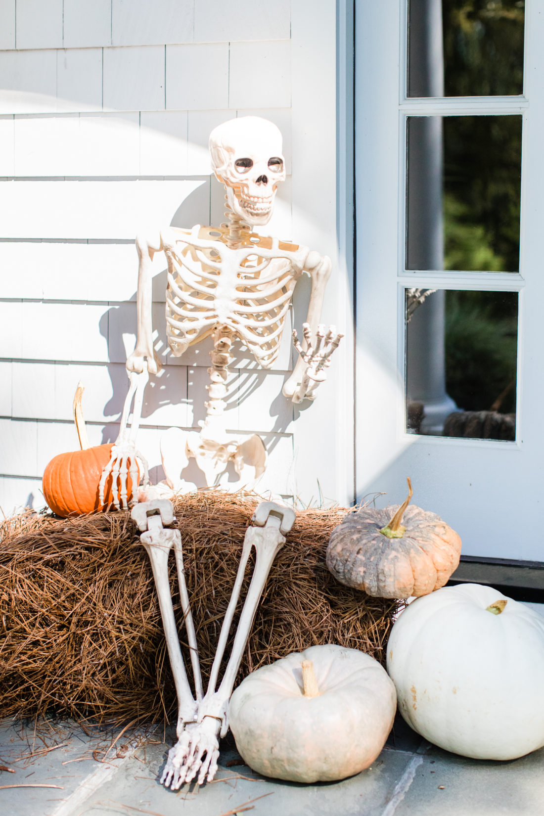 A skeleton sits on a bale of pine needles, surrounded by pumpkins in the spooky entryway of Eva Amurri Martino's Connecticut home
