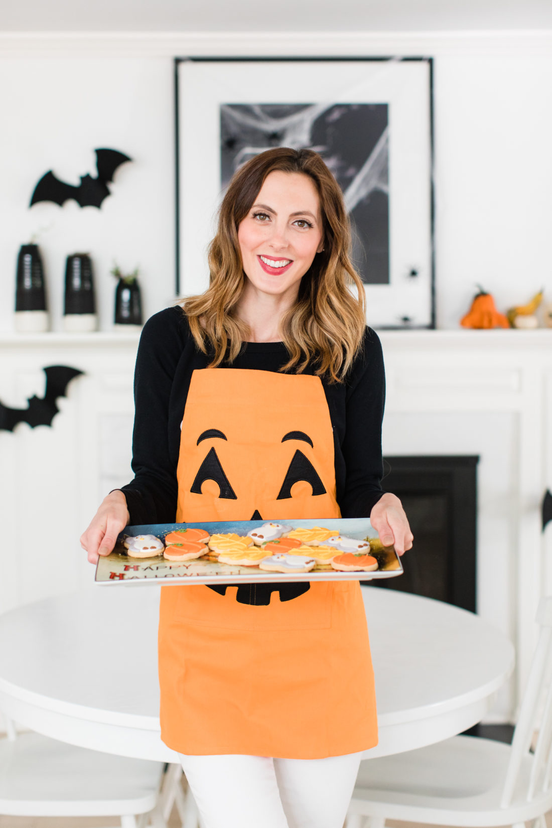 Eva Amurri Martino wears a jack-o-lantern apron and holds a tray of fall-themed cookies for her guests