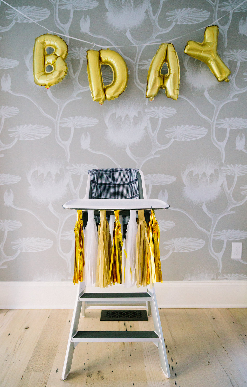 The birthday high chair set up with gold and white tassels at Major Martino's first birthday party in Connecticut