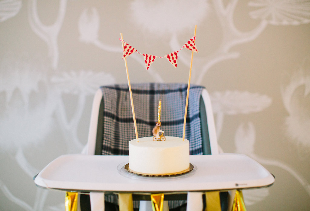 Major Martino's first birthday cake, featuring a red and white patterned flag bunting and a porcelain teddy bear riding a bicycle