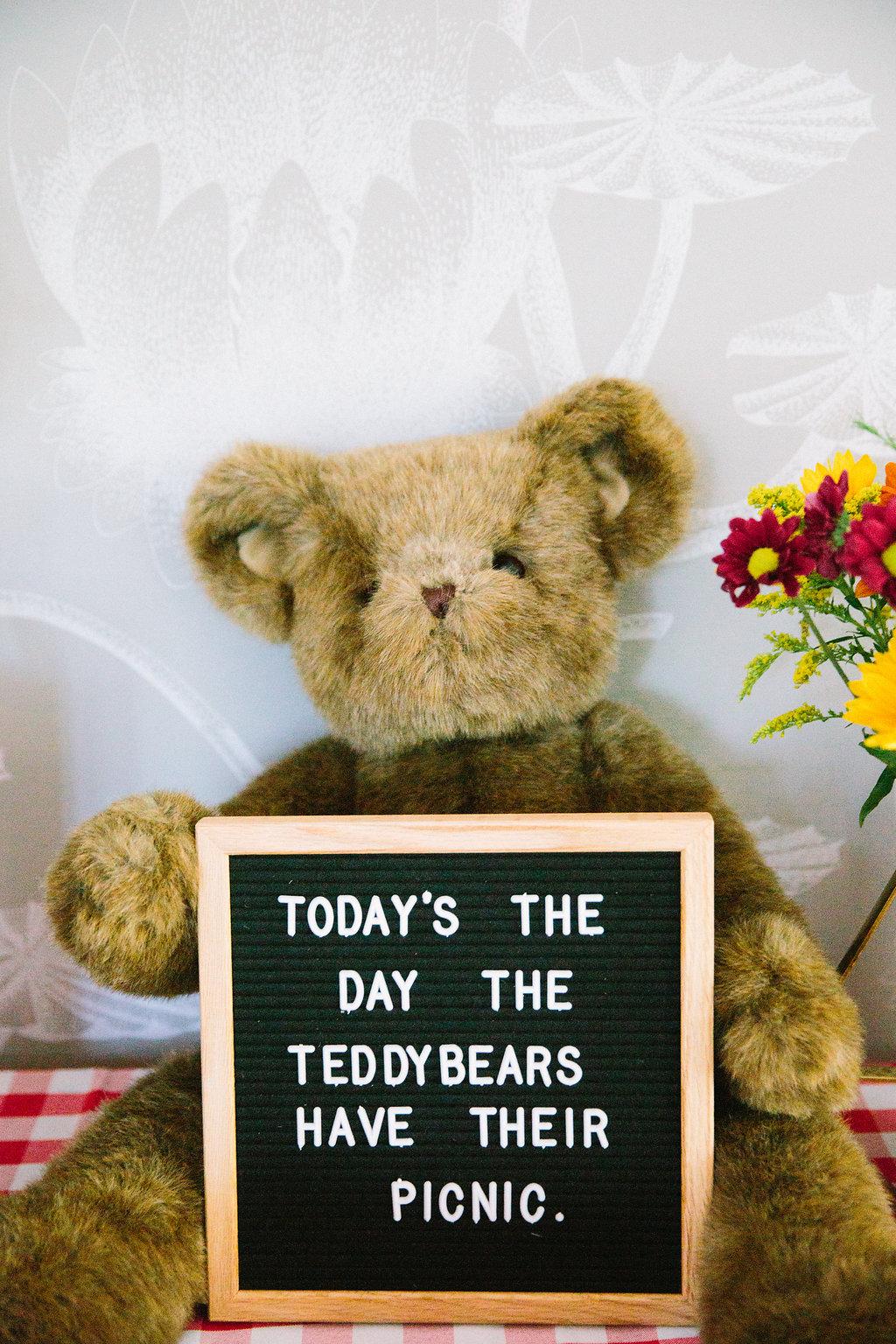 A teddy bear holds a felt board announcing the teddy bear theme of Major Martino's first birthday party
