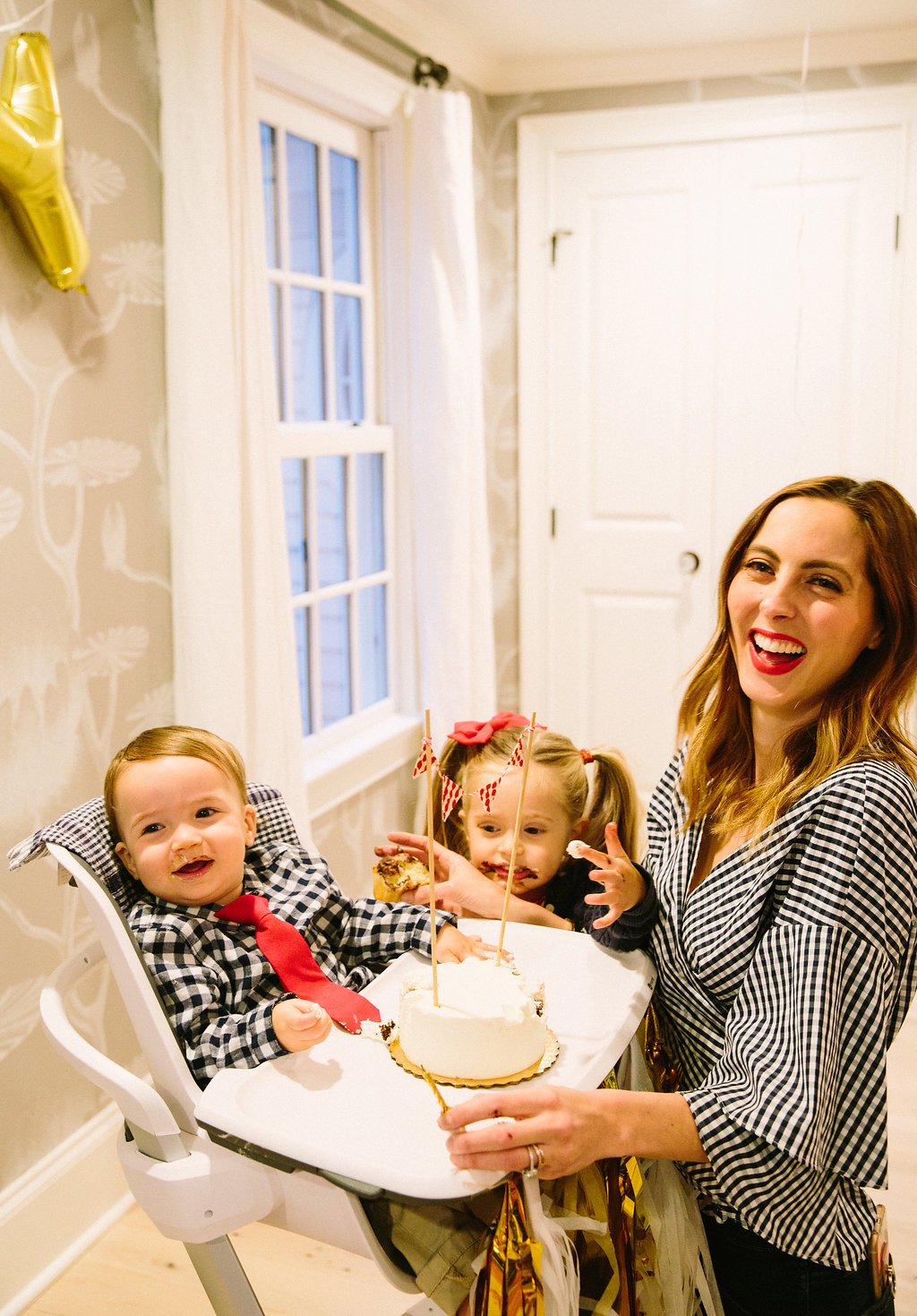 Major Martino laughs as he tries his first bites of cake on his first birthday, surrounded by sister Marlowe and Eva Martino